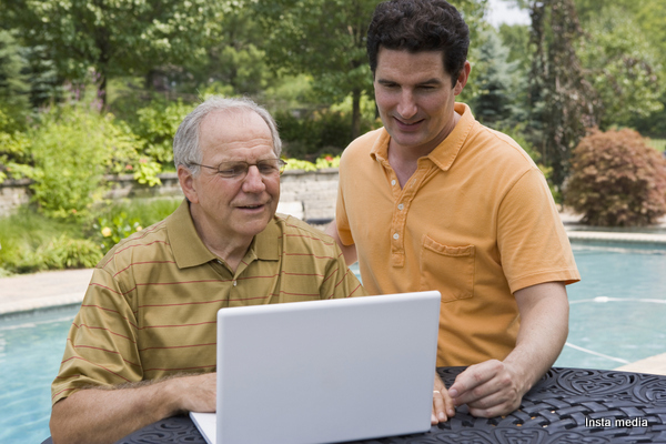 father and son using computer outside
